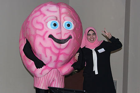 Brain character posing with a woman in a pink headscarf.