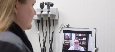 Women talking to a doctor via a computer.