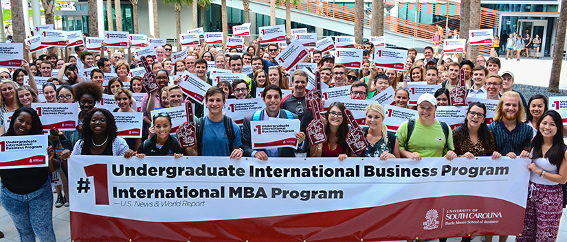 Moore School students in the Palmetto Courtyard holding celebratory No. 1 in international business signs