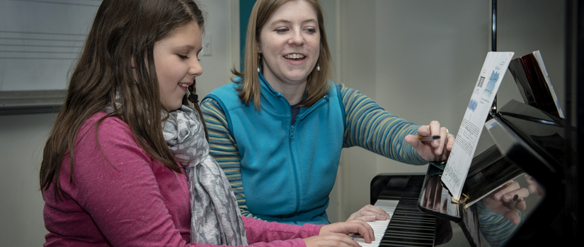 Student teacher and student in piano lesson.