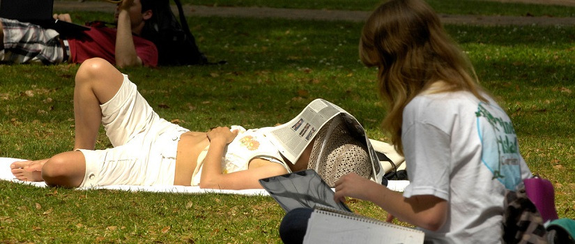 Students in the park. One is napping with a newspaper over his head.