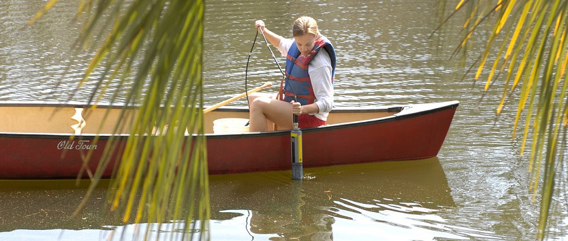 Woman in a kayak pulling a tube out of the water with environmental information