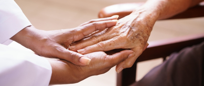 Nursing holding older hands of older patient