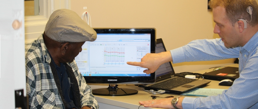Communications Sciences and Disorders faculty member pointing out graphical data on a computer screen to an older gentleman