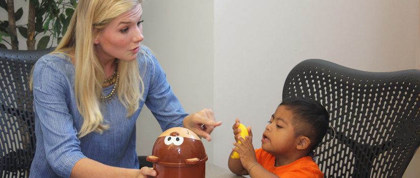 Communications Sciences and Disorders faculty member working with a child