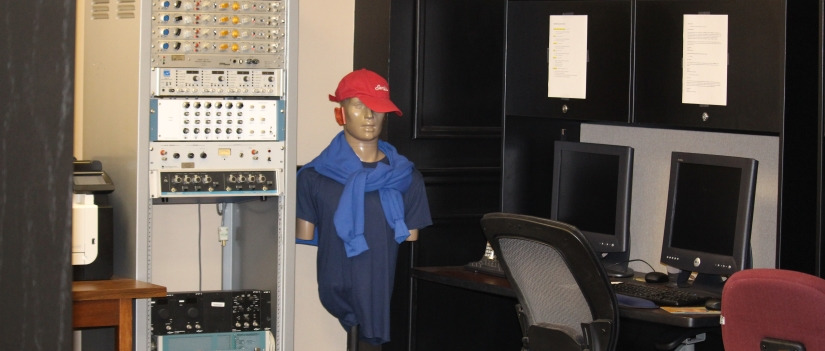 Communication Sciences and Disorders office with computers and a mannequin wearing a hat