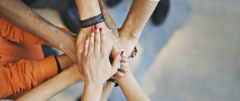 Close up view of people putting their hands together, one on top of the other in the middle of a circle to express teamwork