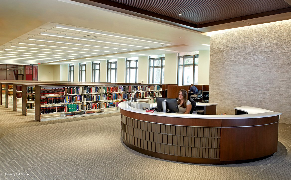 Woman at the front desk of the Law Library with shelves of books in the background.