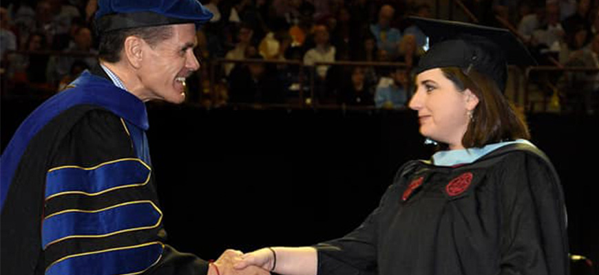 Dean Pedersen shakes Michelle's hand at commencement