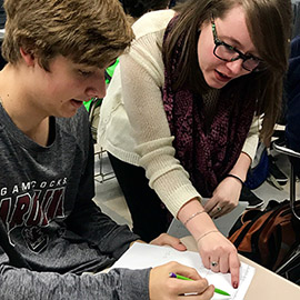 Ms. Schriro works with student in math class