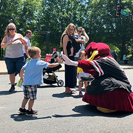Cocky gives young child a high five on Main Street in Greenville