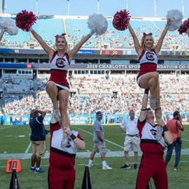 2 UofSC cheerleaders waving their pom poms at the Bank of America Stadium in Charlotte.