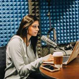 Prer Shidaye in a podcast studio recording The Daily Dos