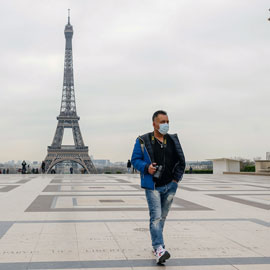 man wearing a face covering walks in Paris with the Eiffel Tower in the background