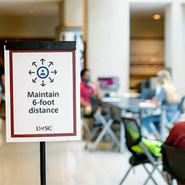 Maintain 6-foot distance sign in front of tables in the Russell House