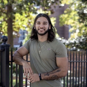 Dawson Tate, First-generation education student. Professional photo outside. Tate is leaning up against a black iron gate on campus