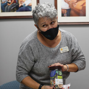Woman with gray hair, gray shirt and black mask standing at a table, displaying health items. Man and woman at table with back to viewer.