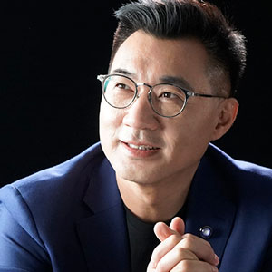 Johnny Chiang looking up, wearing glasses and blue sports jacket