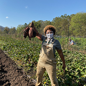 sustainable carolina garden manager sadia pollard holds up vegetables harvested from a garden