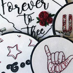 "Four of Allison Lambert's UofSC-themed embroidered artworks, from L to R: ""Go Cocks"" in cursive surrounded by stars, ""Forever to Thee"" beside roses surrounded by the outline of the state of SC, a partial image of an embroidered ""U,"" and the ""Spurs UP"" hand sign with ""Go Cocks"" embroidered inside the palm of the hand"