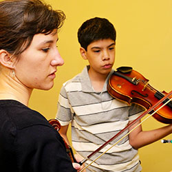 Undergraduate student teaches her student a string instrument